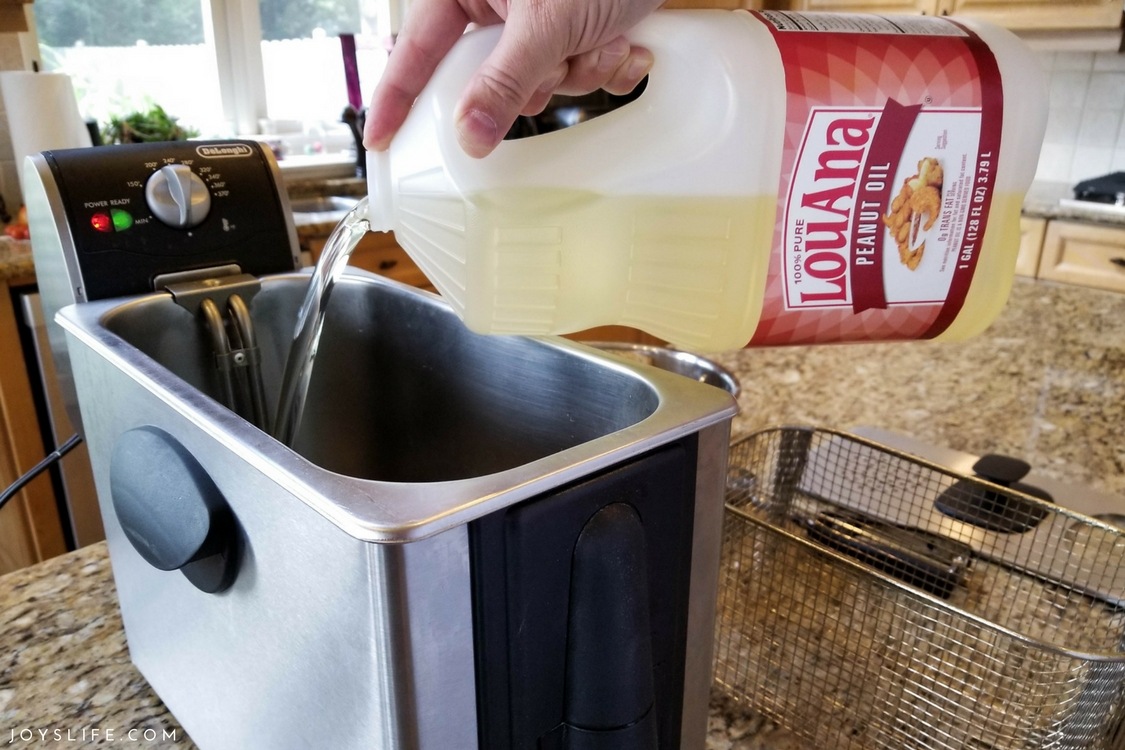 Pouring LouAna Peanut Oil into deep fryer