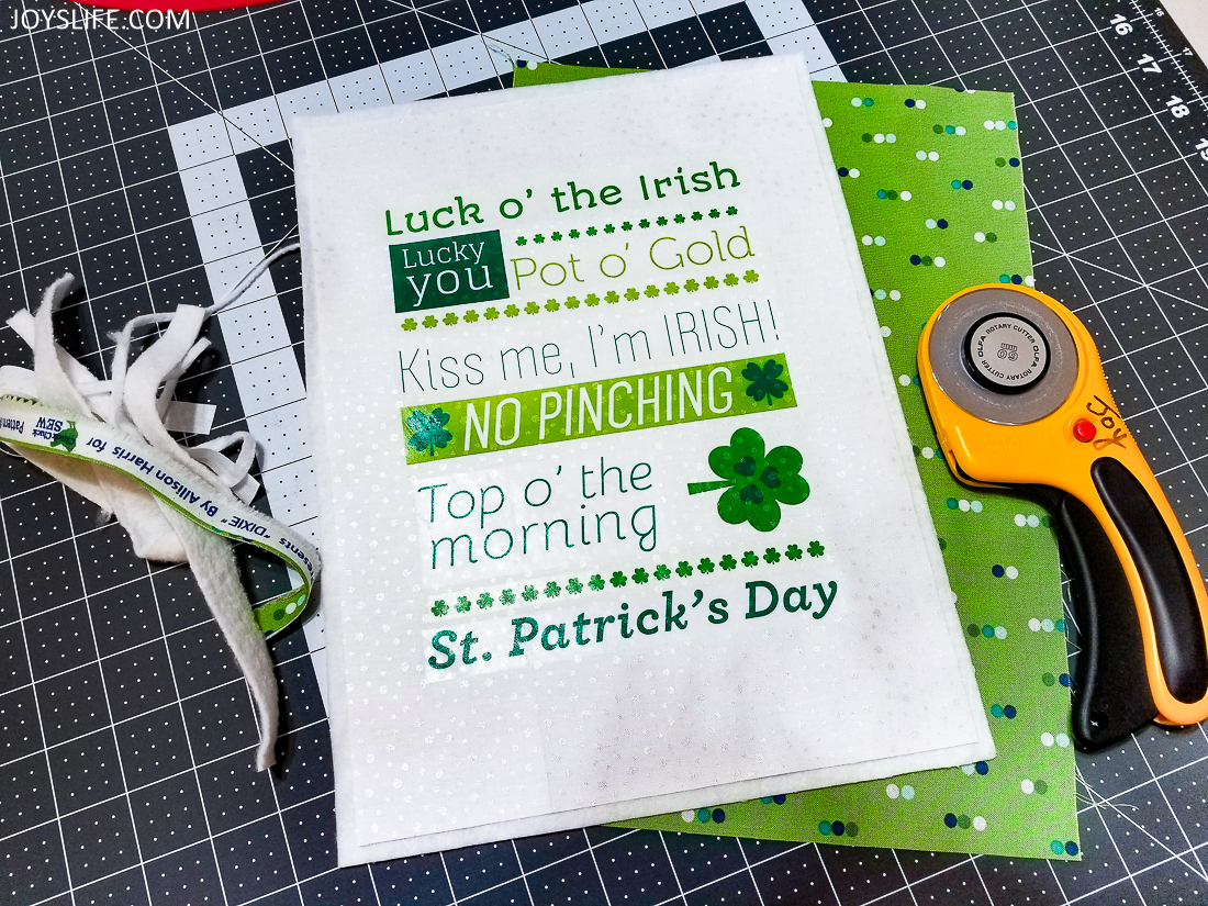 Trimming the fabric of a St. Patrick's Day wall hanging